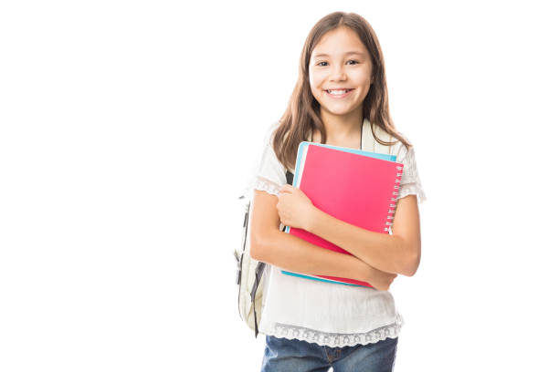 Young hispanic student girl holding books Portrait of smiling school girl child with school bag and books isolated on a white background 8 9 years stock pictures, royalty-free photos & images
