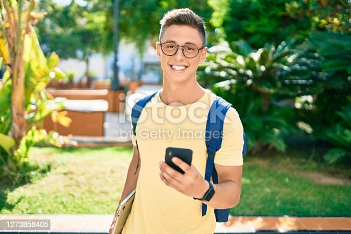 Young hispanic student smiling happy using smartphone walking the university campus