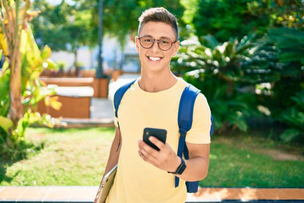 Young hispanic student smiling happy using smartphone walking the university campus stock photo
