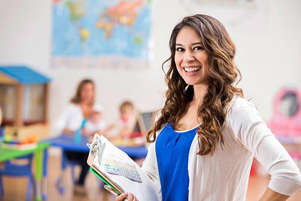 young hispanic teacher smiles in classroom - erzieherin stock-fotos und bilder