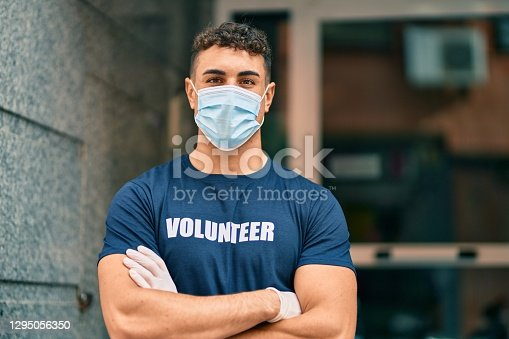 Young hispanic volunteer man with arms crossed wearing medical mask at the city.