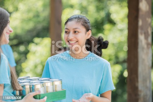 istock Young Hispanic woman collecting cans during a food drive with diverse group of volunteers 1153754008