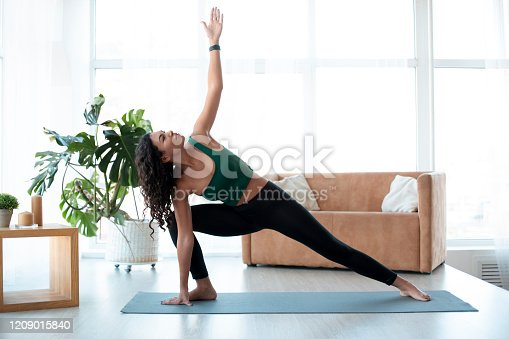 Wellbeing concept. Young Hispanic woman doing yoga at home. Triangle pose