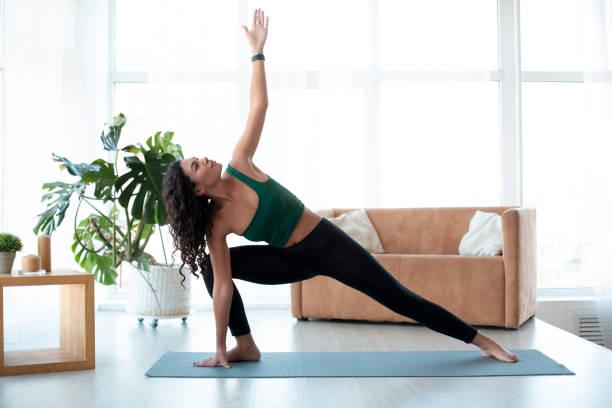 Junge hispanische Frau, die Yoga zu Hause macht. Dreieckspose – Foto