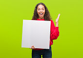 istock Young hispanic woman holding blank banner very happy and excited, winner expression celebrating victory screaming with big smile and raised hands 1044209926