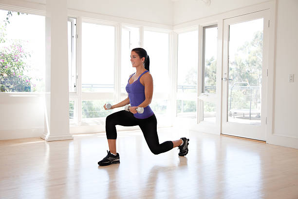 young hispanic woman lifting weights - lunge stock photos and pictures