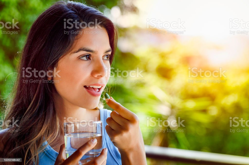 Young Hispanic woman ready taking a pill with a glass of water in hand stock photo