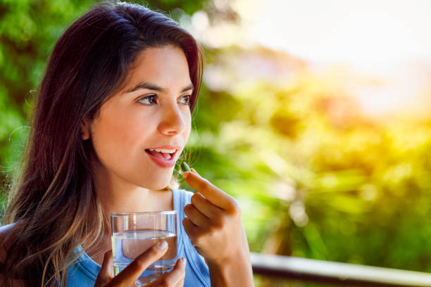 Young Hispanic woman ready taking a pill with a glass of water in hand Health themes. Young Hispanic woman ready taking a pill with a glass of water in hand woman taking pills stock pictures, royalty-free photos & images