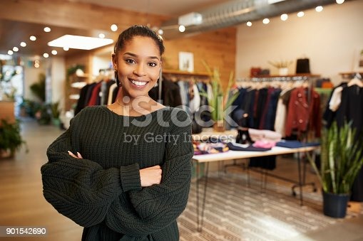 istock Young Hispanic woman smiling to camera in a clothes shop 901542690