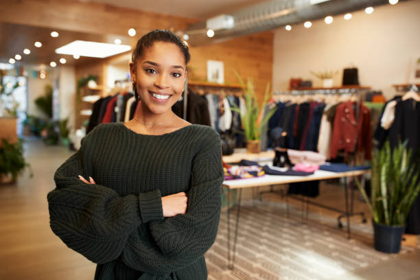 Young Hispanic woman smiling to camera in a clothes shop stock photo