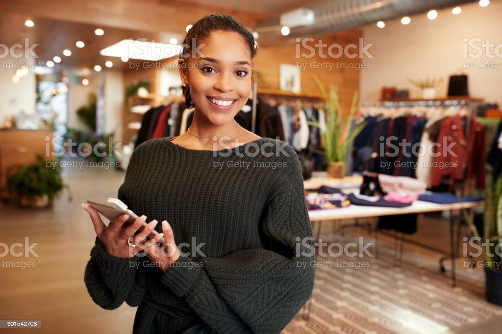 Jonge Spaanse vrouw die lacht om de camera in een kleding winkel foto