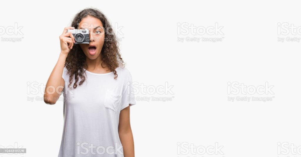 Young hispanic woman taking pictures using vintage camera scared in...