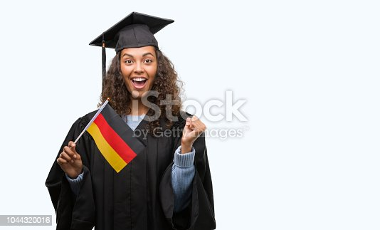 1175468850istockphoto Young hispanic woman wearing graduation uniform holding flag of Germany screaming proud and celebrating victory and success very excited, cheering emotion 1044320016