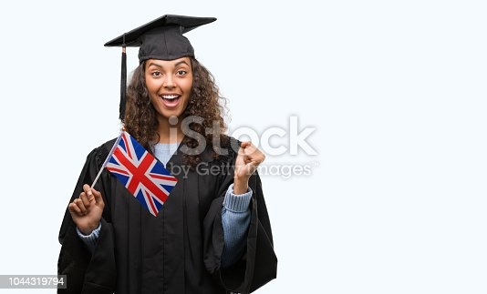 1175468850istockphoto Young hispanic woman wearing graduation uniform holding flag of UK screaming proud and celebrating victory and success very excited, cheering emotion 1044319794