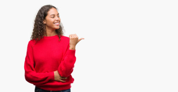 Young hispanic woman wearing red sweater smiling with happy face looking and pointing to the side with thumb up. Young hispanic woman wearing red sweater smiling with happy face looking and pointing to the side with thumb up. red shirt stock pictures, royalty-free photos & images