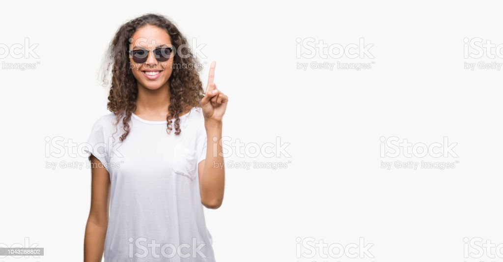 Young hispanic woman wearing sunglasses showing and pointing up with finger number one while smiling confident and happy. stock photo