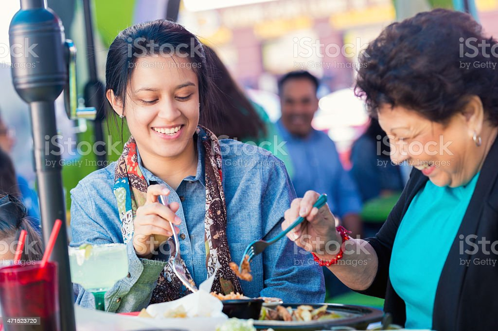 Young Hispanic woman with grandmother at Tex-Mex restaurant stock photo