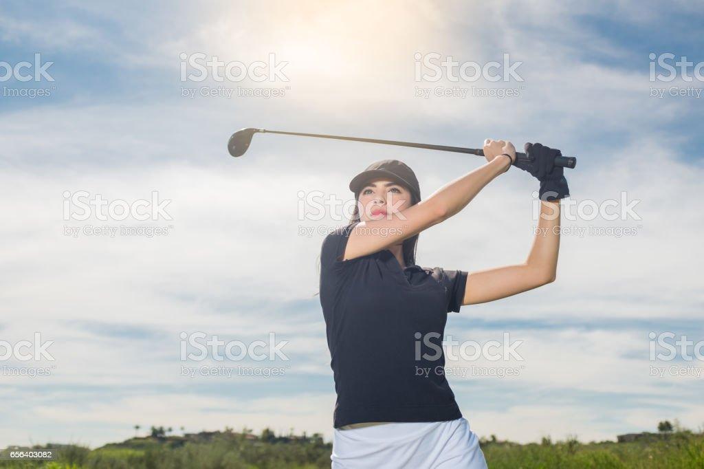 Young Hispanic Women Hitting A Golf Ball stock photo
