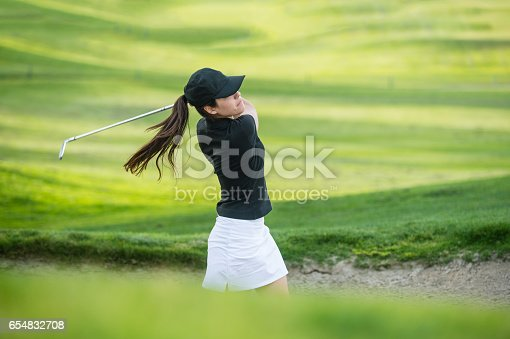 istock Young Hispanic Women Hitting The Ball Out Of A Bunker 654832708