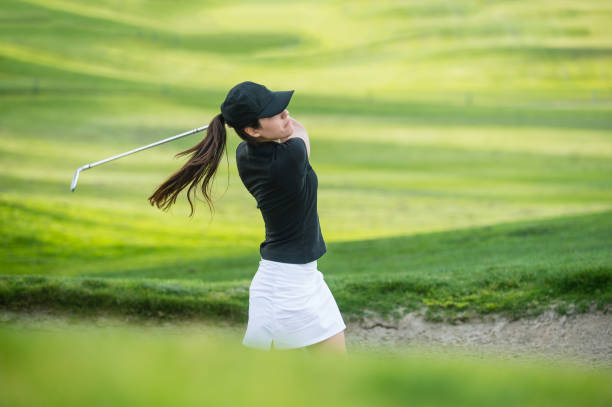 young hispanic women hitting the ball out of a bunker - female golfer stock photos and pictures