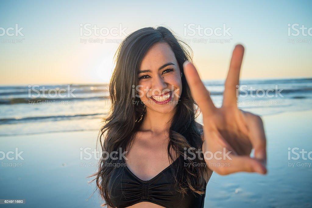 Young Hispanic Women On The Beach Peace Sign - Photo