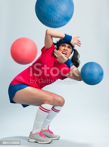 Young Hispanic Women Playing Dodgeball in a retro gym outfit with multipe balls thrown at her.