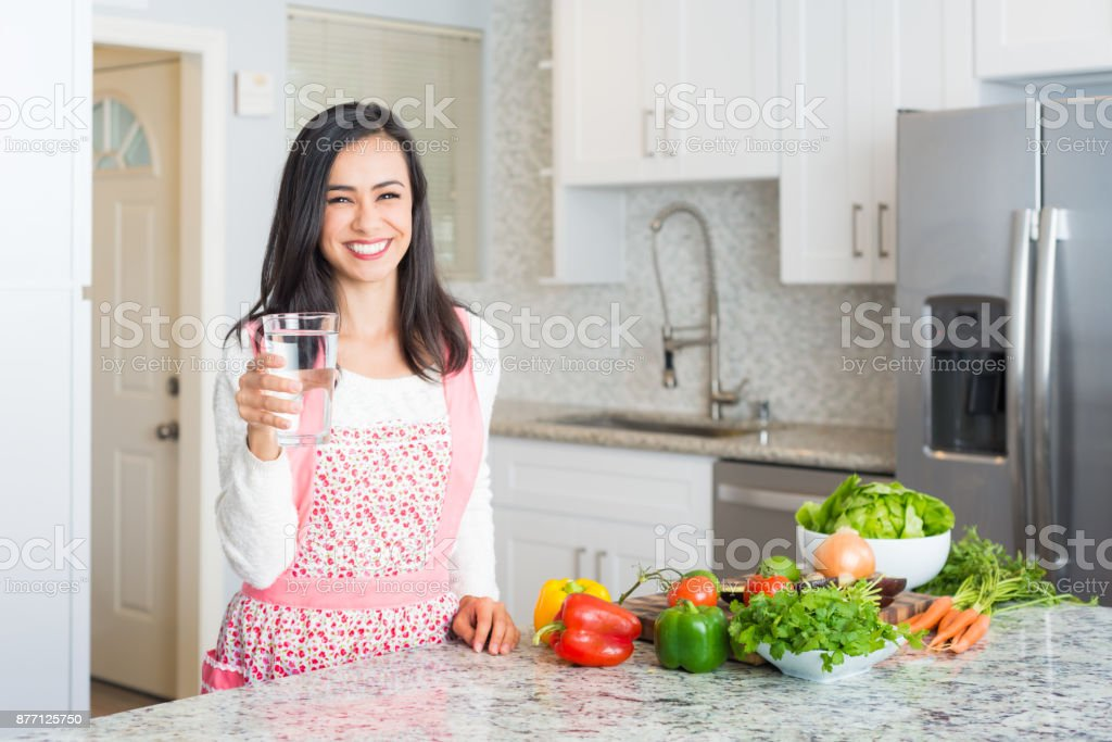 Young Hispanic Women Preparing a Meal Holding A Glass Of Water stock photo
