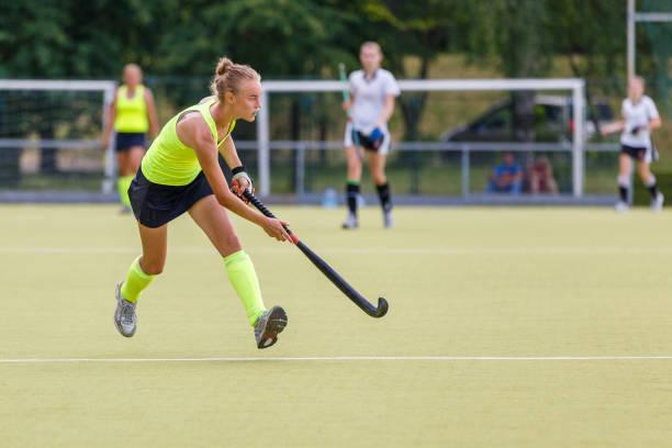 jonge hockey speler vrouw met bal in de aanval - samen sporten stockfoto's en -beelden