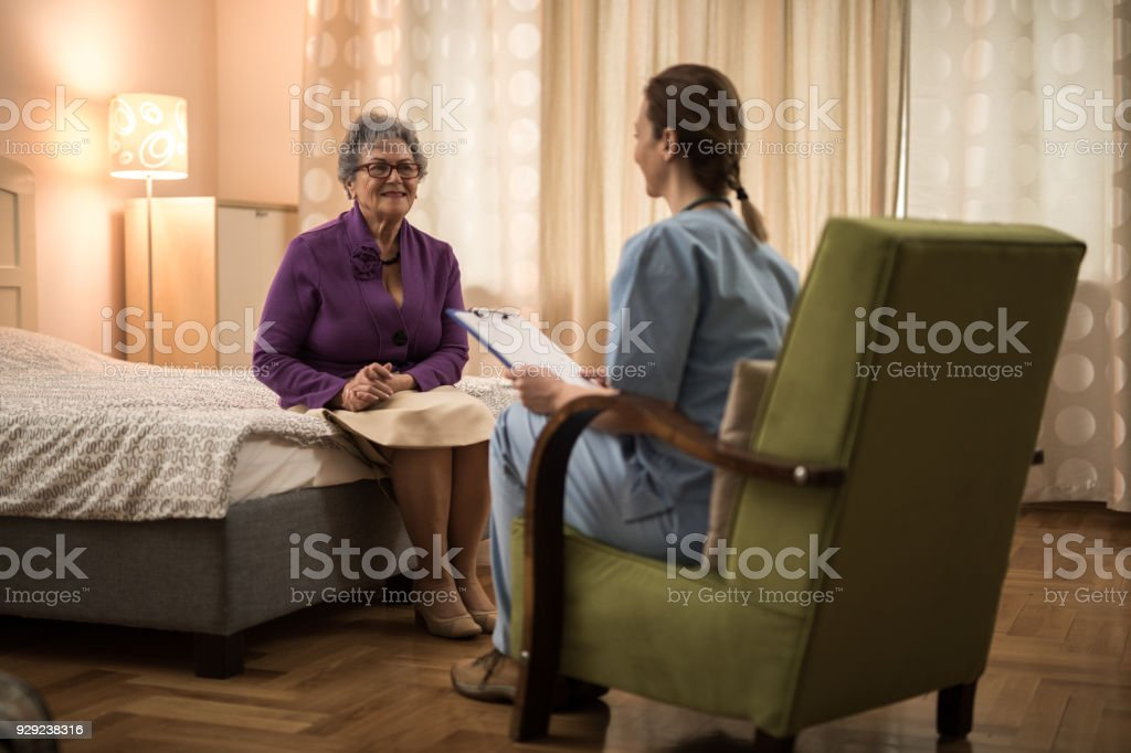 Senior women sitting on bed and listening a young nurse wich reading...