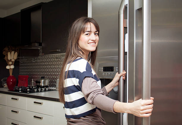 Young home maker checks the contents of her refrigerator, stock photo