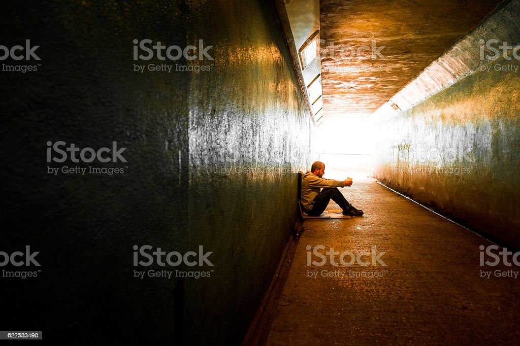 Young homeless adult male sitting and begging in subway tunnel stock photo