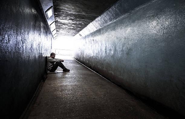 young homeless adult male sitting in subway tunnel - niederlage stock-fotos und bilder