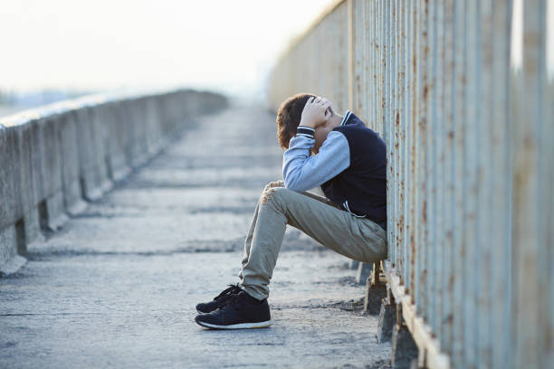 young homeless boy  crying on the bridge stock photo