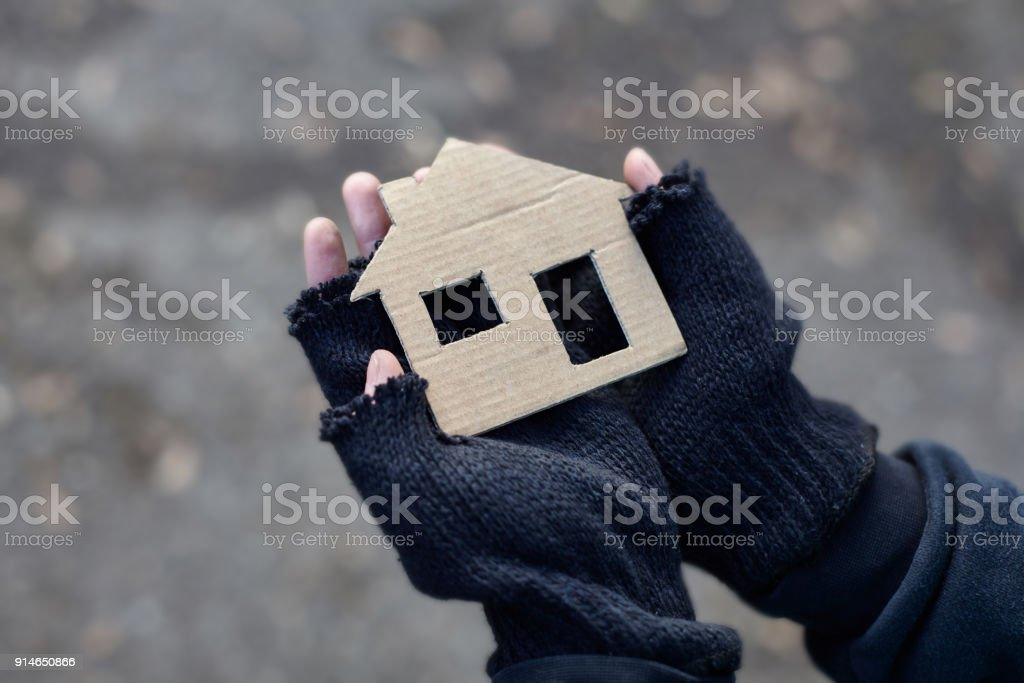 young homeless boy holding a cardboard house stock photo