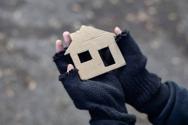 young homeless boy holding a cardboard house - homelessness stock photos and pictures