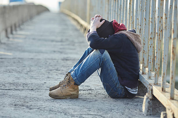 young homeless boy sleeping on the bridge - homelessness stock photos and pictures