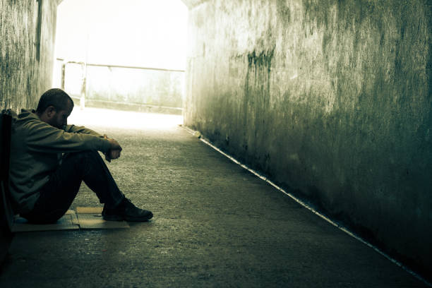 young homeless caucasian male sitting in dark subway tunnel - psychiatric ward stock photos and pictures