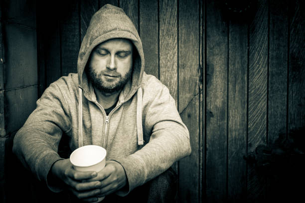 young homeless caucasian male sitting in doorway begging for money - psychiatric ward stock photos and pictures