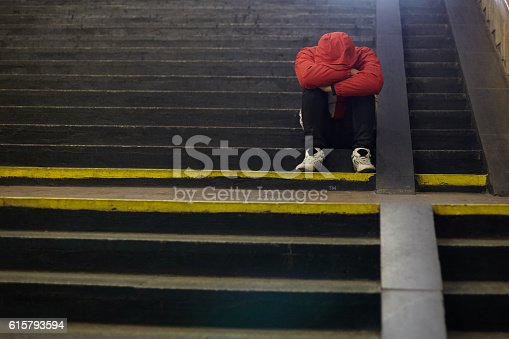 istock young homeless man sleeping on the street 615793594