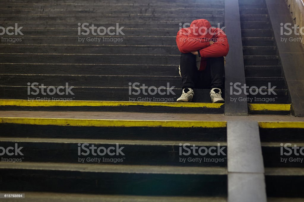 young homeless man sleeping on the street stock photo
