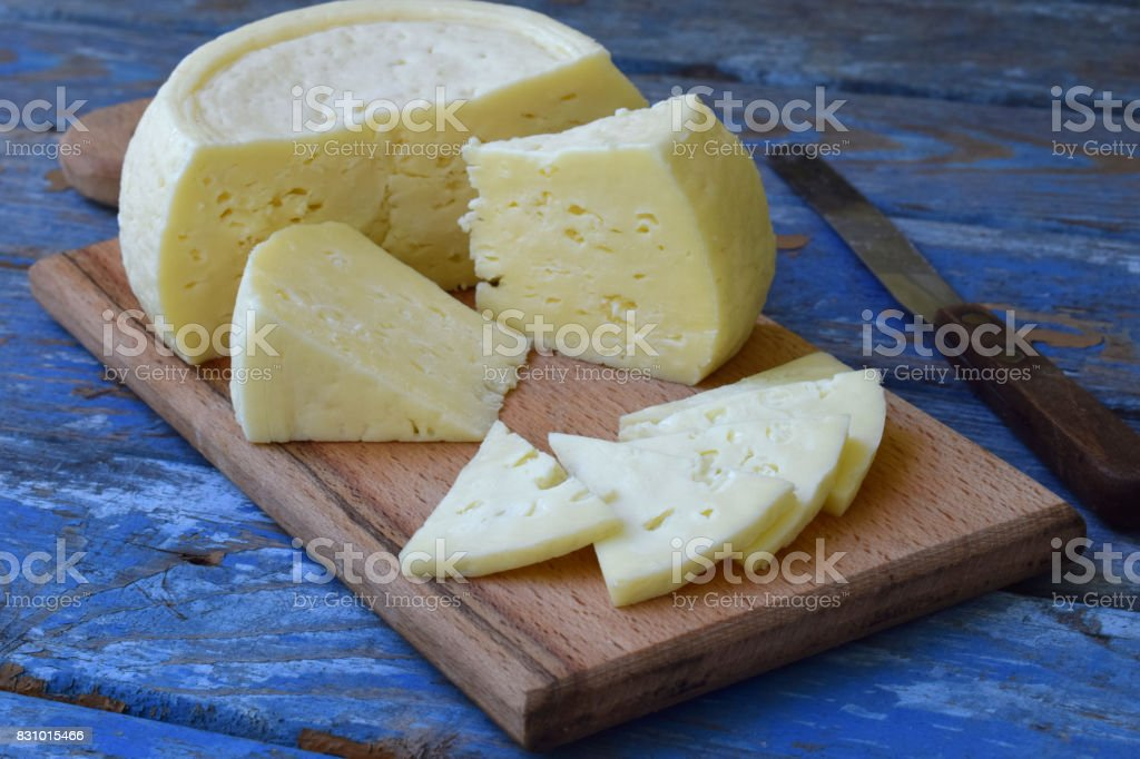 young homemade cheese on a blue wooden background. Bio organic food. stock photo