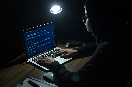 istock Young hooded woman hacker doing cyber attack 954683360
