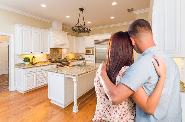Young Hopeful Military Couple Looking At Custom Kitchen Young Hopeful Military Couple Looking At Beautiful Custom Kitchen. model home stock pictures, royalty-free photos & images