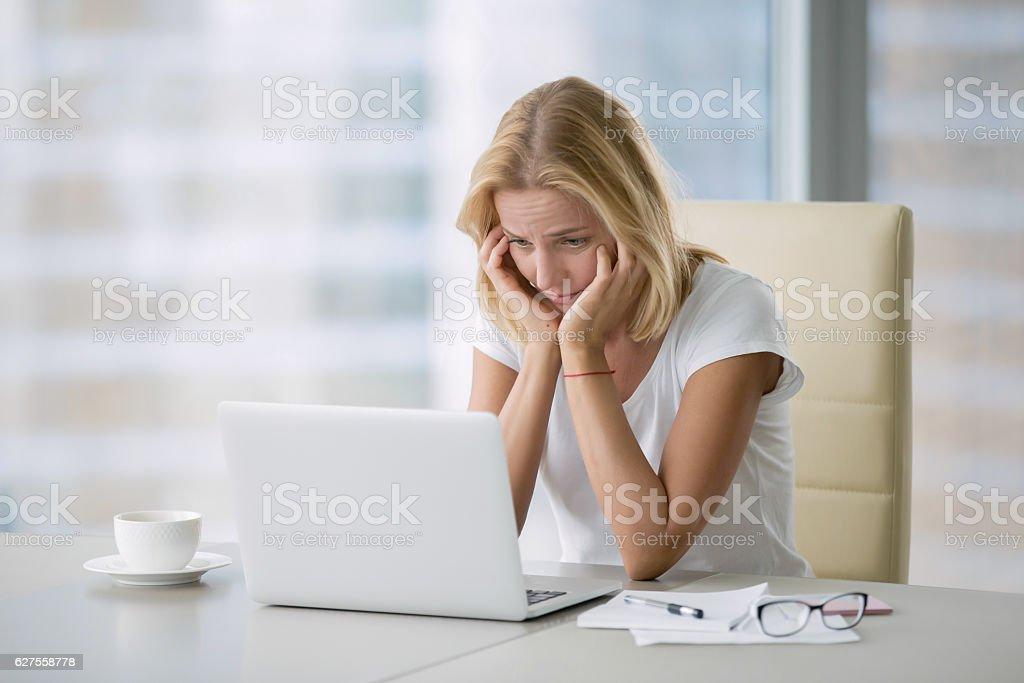 Young hopeless woman at laptop stock photo