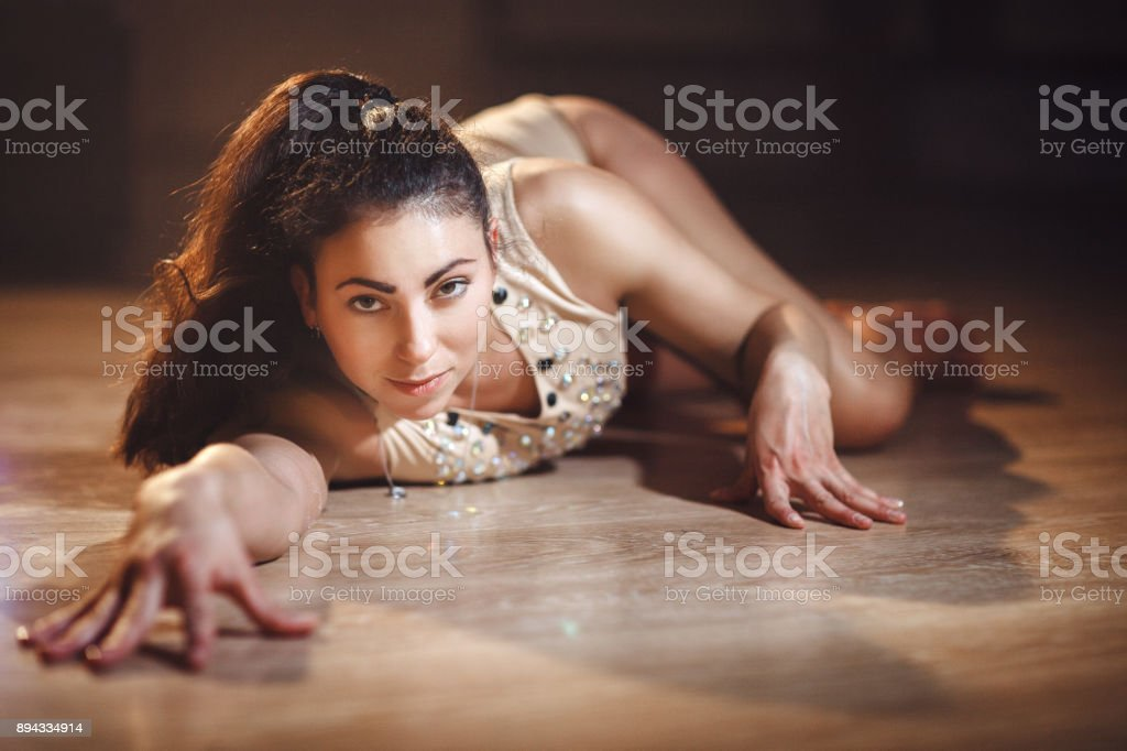 Young hot woman in sexy lingerie performs sensual pole dance. Go-go dancer  on a floor. - Stock image .
