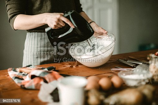 Young woman in kitchen using mixer for wiped cream