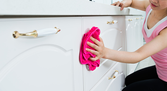 Young housewife cleaning the kitchen with a pink cloth