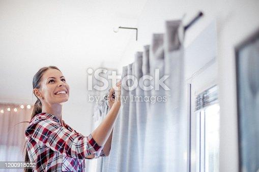 Beautiful Caucasian smiling woman in casual clothes is hanging curtains after washing at cozy home.