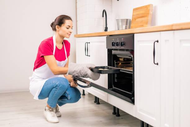 Junge Hausfrau hocken beim Puten Tablett mit rohen Keksen in elektroelektrischen Ofen – Foto