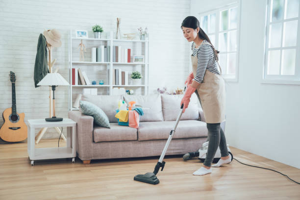 young housewife using vacuum cleaner cleaning stock photo